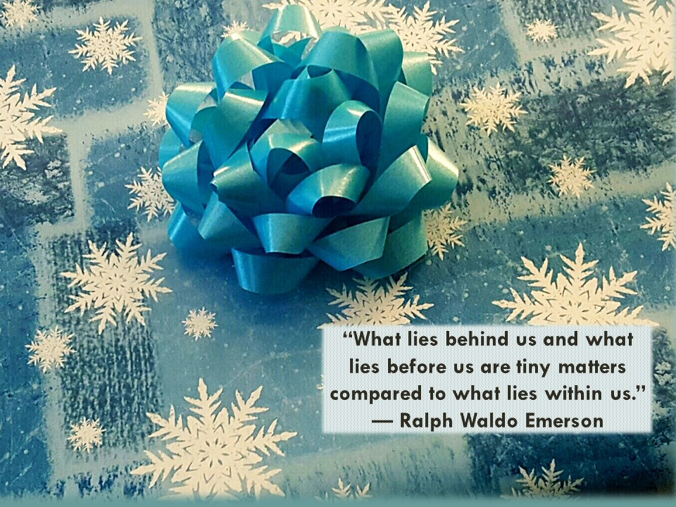 photo of a wrapped gift with snowflake wrapping paper and a blue bow on top