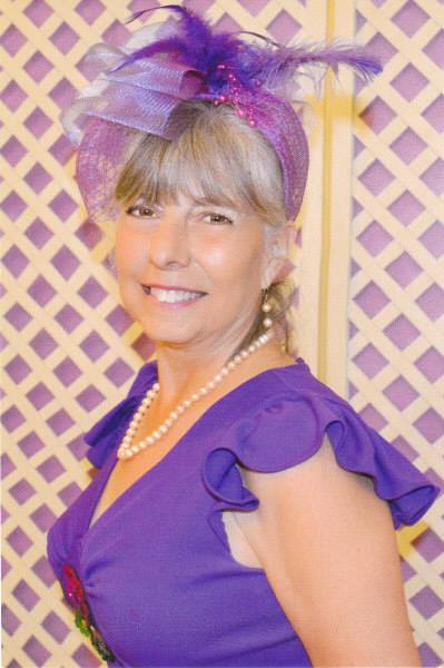 Marie Fostino Facebook profile photo dressed in purple with feather  band in her hair