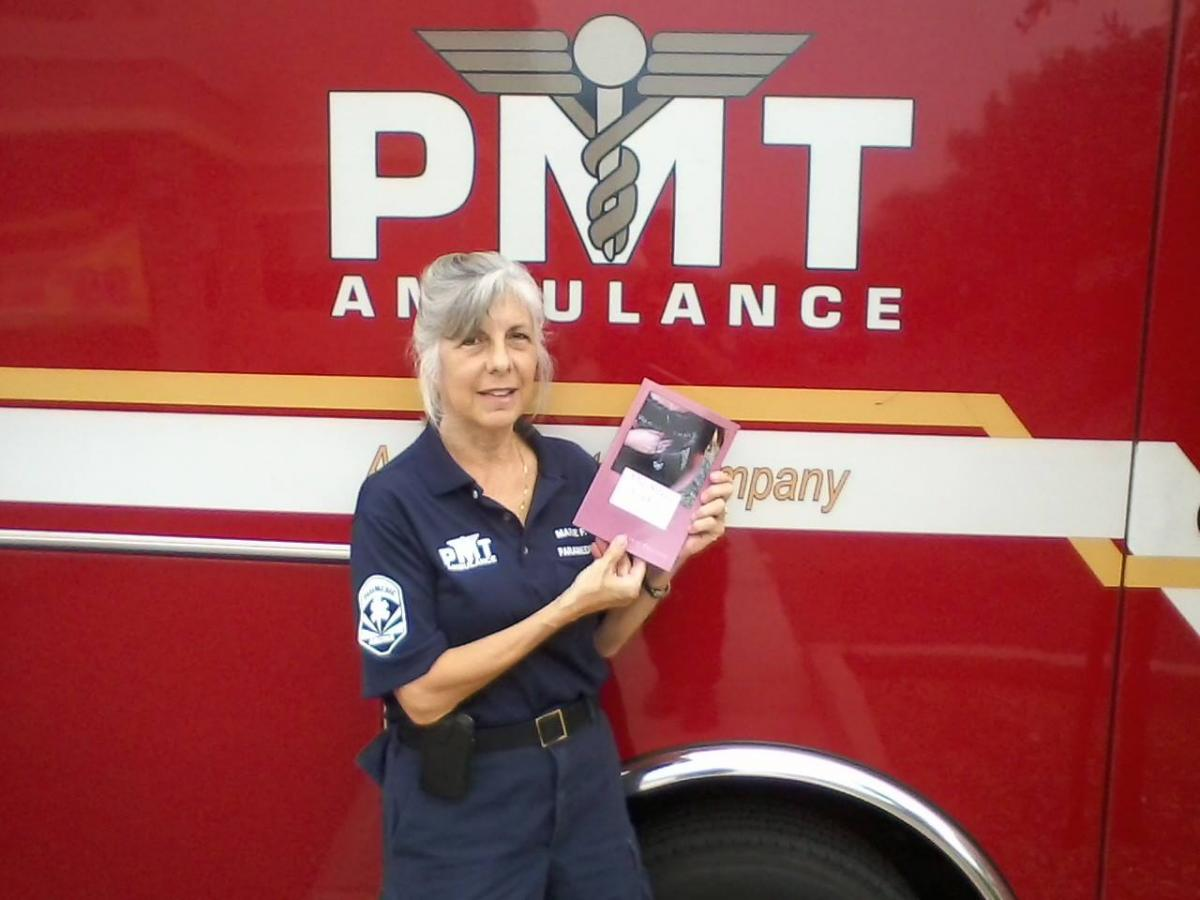 Marie Fostino in standing by her ambulance holding the first book she wrote