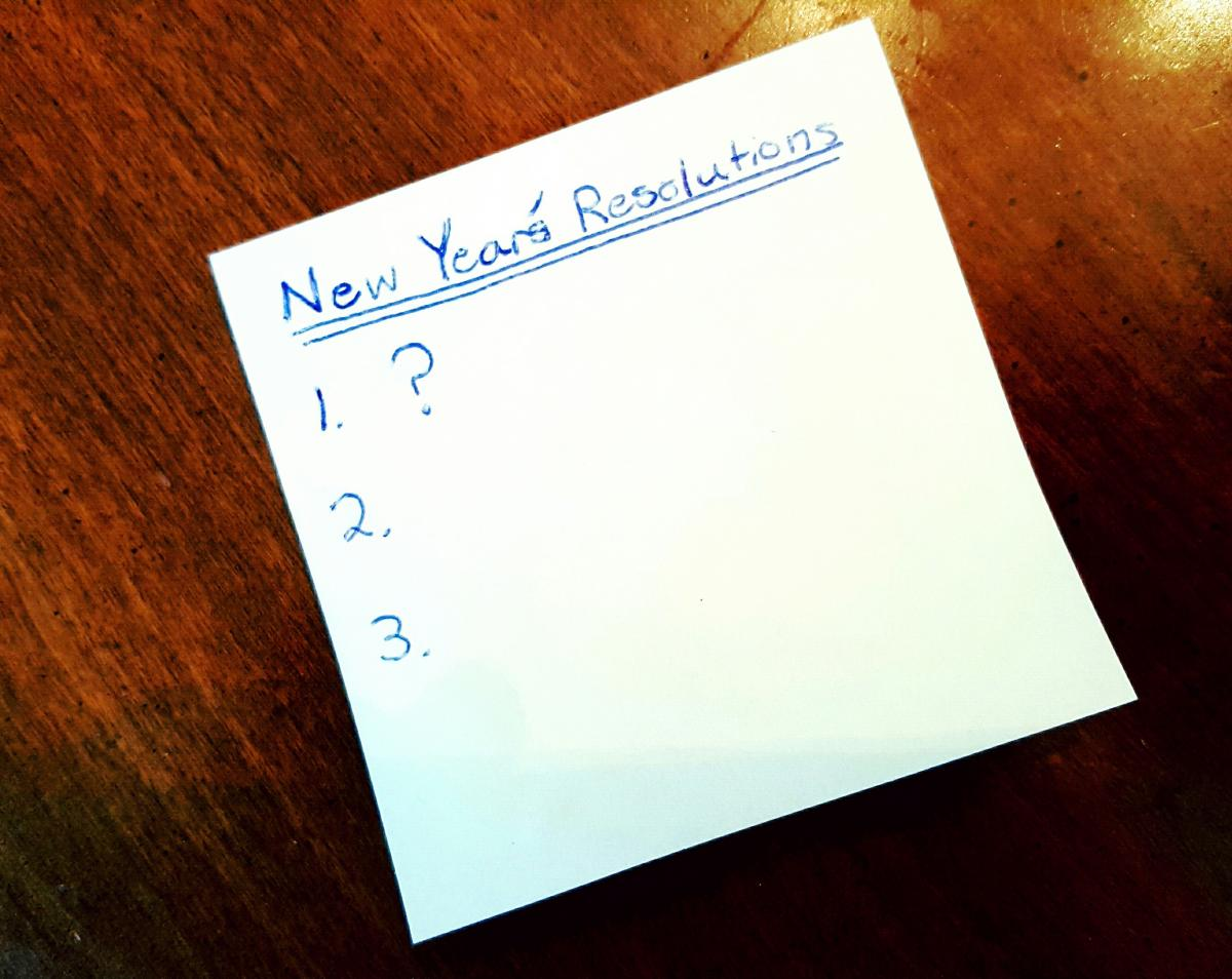 Photo of note pad on table with the words - New Year's Resolutions