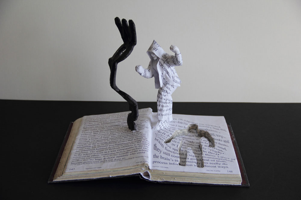 Jim McCarthy's sculpture entitled fighting with words- Sculpted image of man cut out of pages in a book arms raised in fighting stance
